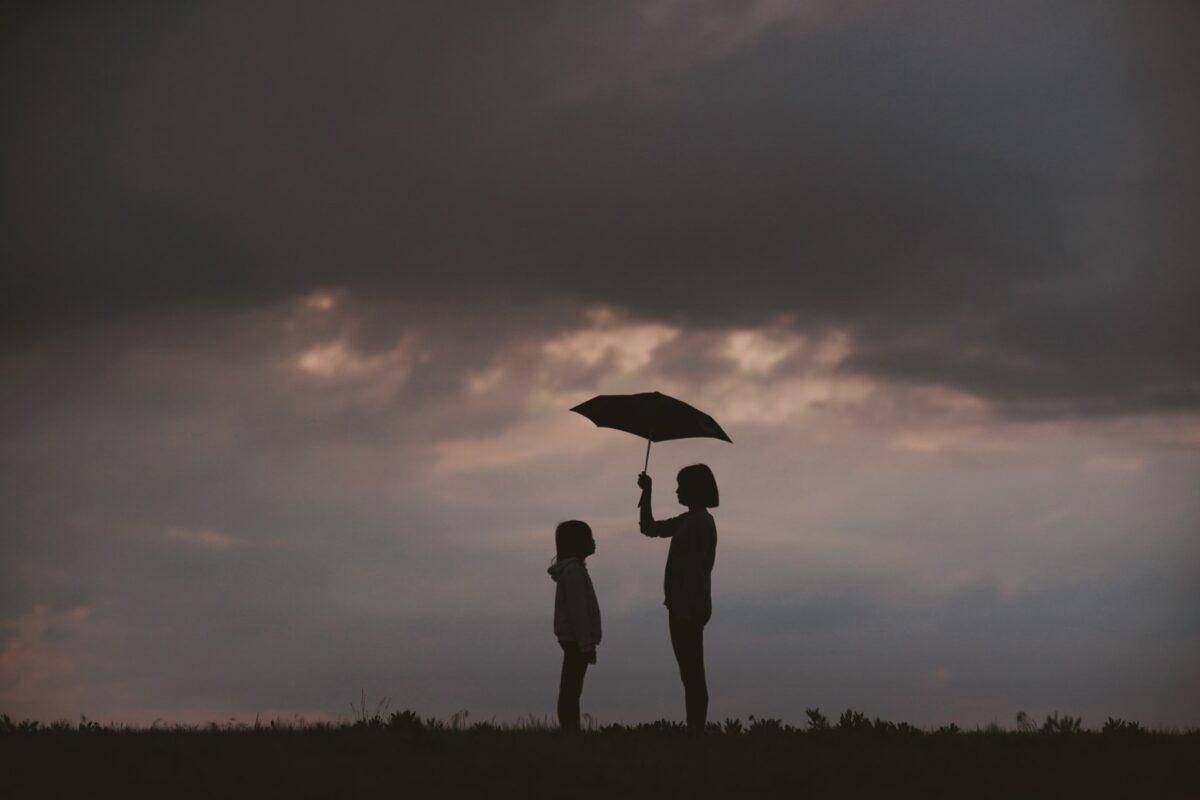 Sotto un cielo di nuvole nere, una ragazzina copre con l'ombrello una bambina